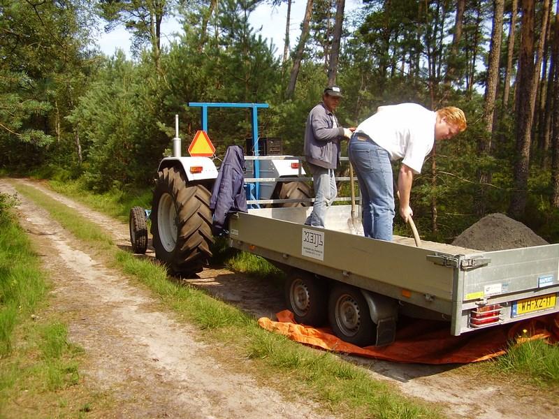 Rinus Keijl en medewerker Klaas lossen hier de aanhanger die gevuld was met betonzand