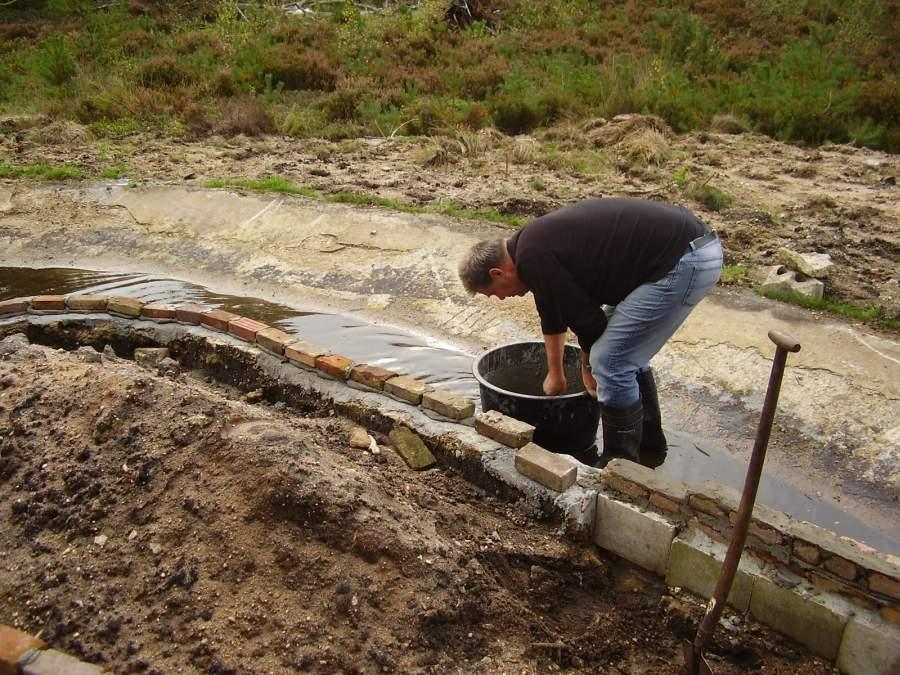 Henk Bouw, repareert eiland in vijver Halve Maan